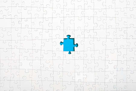 Missing white jigsaw puzzle pieces on blue background copy space for your text. Business concept.