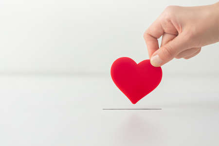 The concept of charity, love, donate and helping hand. Woman's hand places heart in the donation slot. Donor of blood or human organs, saving lives. Stock Photo