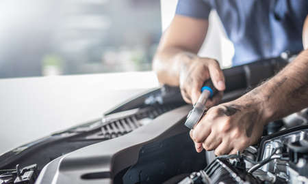 Auto mechanic working and repair on car engine in mechanics garage. Car service. Man with wrench at workshop.