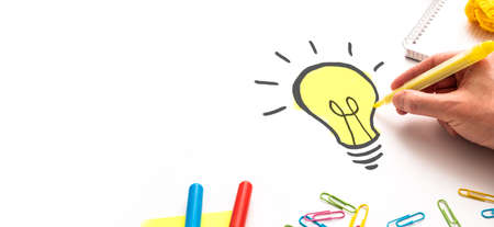 Creative new idea. Innovation, brainstorming, inspiration and solution concepts. Designer drawing a light bulb.