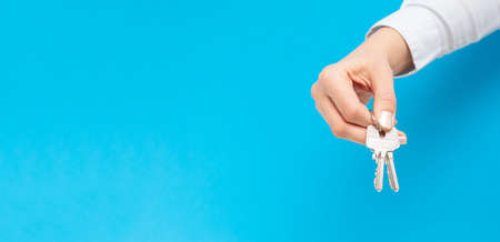 Female hand holding and giving house key on copy space background. Real estate agent. Banque d'images