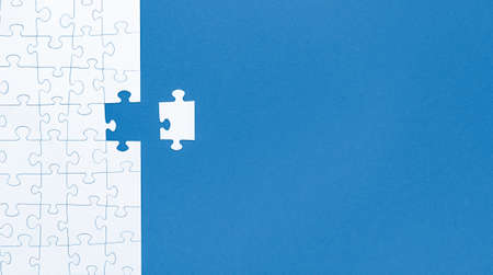 White jigsaw puzzle pieces on blue background copy space for your text. Business concept. 写真素材