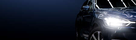 Black modern car closeup on black background.