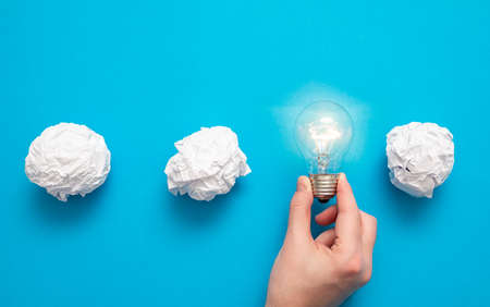 Creative new idea. Innovation, brainstorming, inspiration and solution concepts. Light bulb and crumpled paper on blue background.