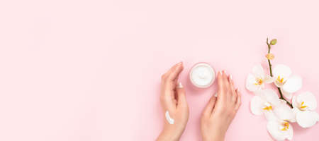 Woman applying moisturizing cream on hands. Cosmetic cream lotion concept.