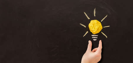 Creative new idea. Innovation, brainstorming, inspiration and solution concepts. Light bulb with crumpled paper on blackboard background. 写真素材