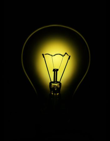 Bulb backlit with yellow light on black background Stock Photo