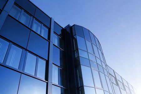 Angled shot of an office building with shiny blue glass facade
