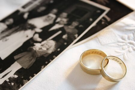 Old wedding rings and out of focus black and white photograph of a wedding