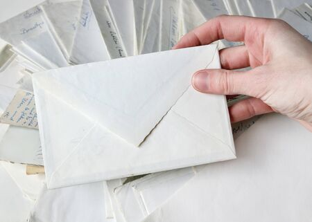 Hand holding a blank white envelope. Many other letters visible in the background
