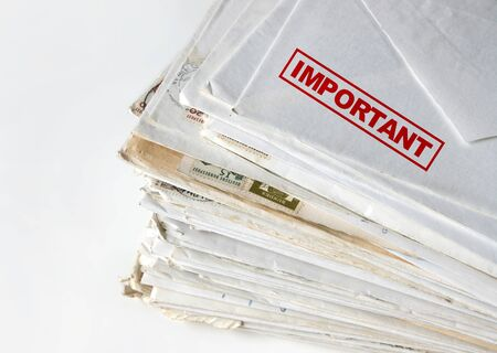 Big stack of letters and envelopes on a desk, top letter labeled as important