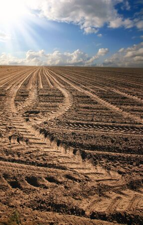Tire tracks in the raw earth of a freshly plowed field
