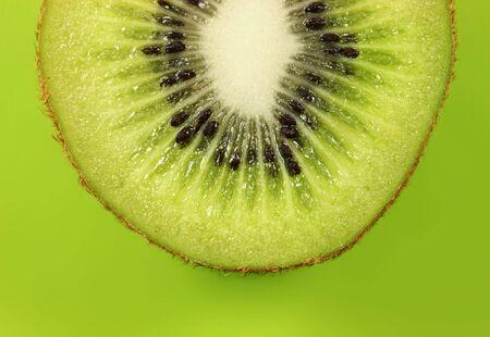 Kiwi half on lush green background. Stock Photo