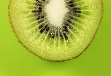 Kiwi half on lush green background. Stock Photo