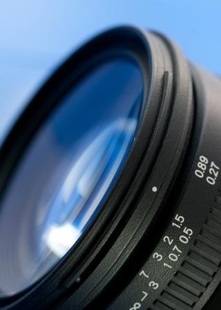 Closeup of a camera lens against blue background Stock Photo