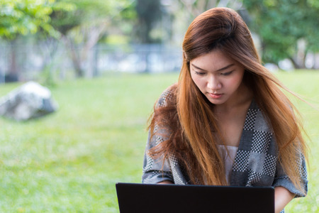 breeze: Asian woman working on a laptop at a garden or park with little breeze