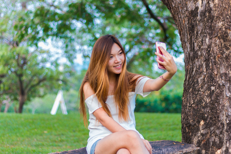 breeze: Asian woman playing smartphone selfie at a garden or park under the tree with little breeze Stock Photo