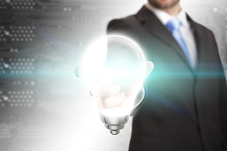 Business man holding a lightbulb in his hand photo