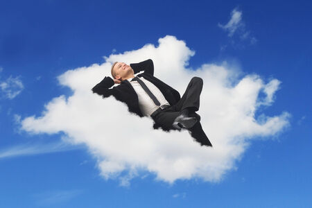 Businessman sleeping in a cloud dreaming about his holidays photo