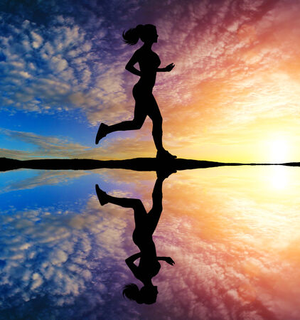 Girl running at sunset with reflection in water photo