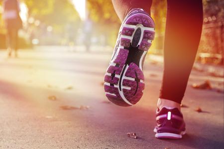mujeres corriendo: Muchacha de la aptitud ejecutando al atardecer en el centro de la ciudad