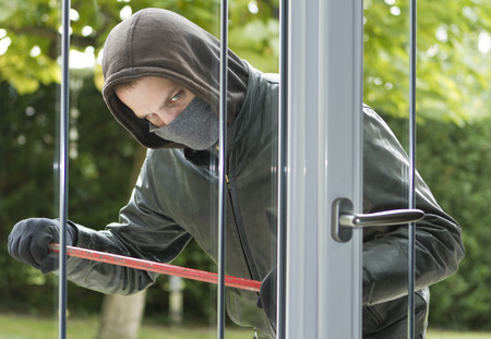 offence: Burglar wearing black clothes and leather coat breaking in a house