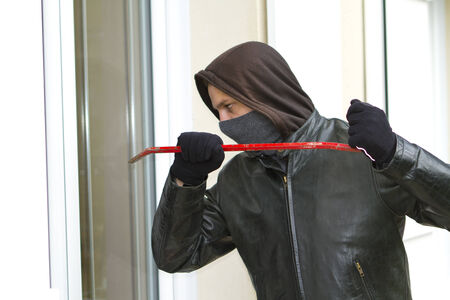 Burglar wearing black clothes and leather coat breaking in a house photo