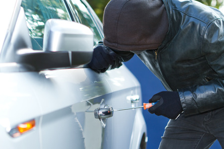 Thief wearing black clothes and leather coat stealing a car Stock Photo