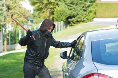 Thief wearing black clothes and leather coat stealing a car photo