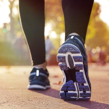 Fitness Girl running at sunset in city center photo