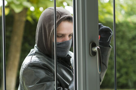 breaking in: Burglar wearing black clothes and leather coat breaking in a house