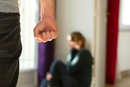 agression: Man beating up his wife illustrating domestic violence
