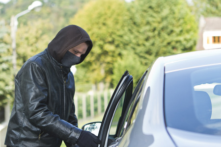 leather coat: Thief wearing black clothes and leather coat stealing a car Stock Photo