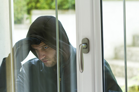 delinquent: Burglar wearing black clothes and leather coat breaking in a house