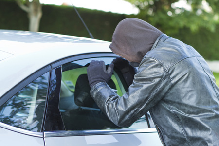 delinquent: Thief wearing black clothes and leather coat stealing a car Stock Photo