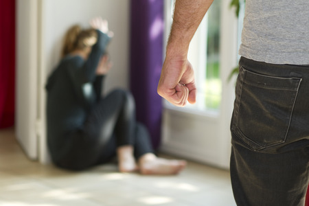 panicked: Man beating up his wife illustrating domestic violence