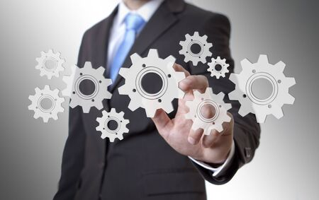 Businessman playing with gears and various cogwheels Stock Photo