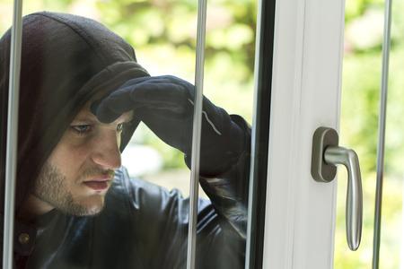 Inbreker het dragen van zwarte kleding en lederen jas breken in een huis