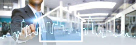 Businessman drawing a house with his finger on a tactile screen Stock Photo
