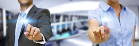 businesspartners: Man and woman using digital interfacein large blue office Stock Photo
