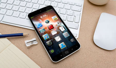 tactile: Workplace with mobile phone on table close-up Stock Photo