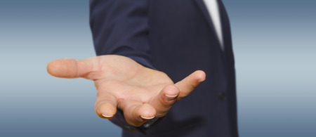 arm of a man: Businessman showing empty hand wearing deep blue suit Stock Photo