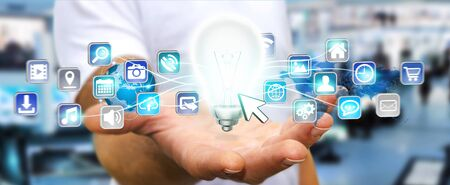 shinny: Young man holding shinny lightbulb in his hand with digital icons flying around Stock Photo
