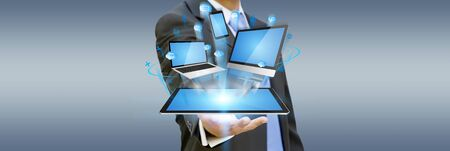 Businessman with computer phone and tablet in his hand Stock Photo