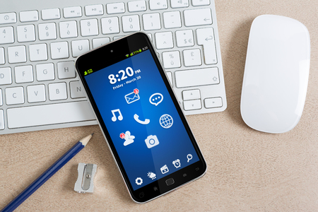 tactile: Workplace with modern mobile phone on table close-up