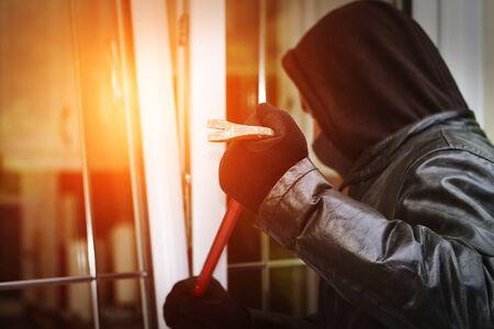 Cambrioleur porter des vêtements noirs et de rupture de manteau de cuir dans une maison