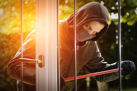 Burglar vestita di nero e cuoio cappotto di rottura in una casa