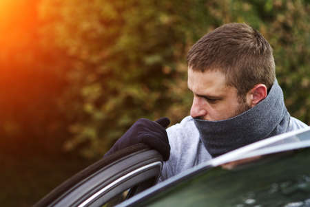 delinquency: Thief wearing black clothes and leather coat stealing a car Stock Photo