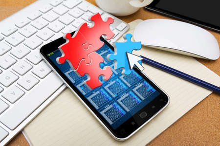 smart investing: Modern mobile phone in office with puzzle icons flying over Stock Photo
