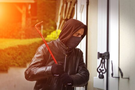 house coat: Burglar wearing black clothes and leather coat breaking in a house